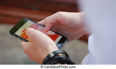 Close-up of male hands tapping on smartphone, scrolling analytics, diagrams, charts