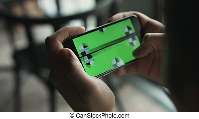 Close-up of male hands touching green screen on mobile phone. Guy zoom in and zoom out picture.  Green screen Chroma Key. Close up. Tracking motion. Horizontal   pants - Swipe left   right animation
