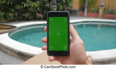 Close-up of male hands touching of smartphone at vacation...