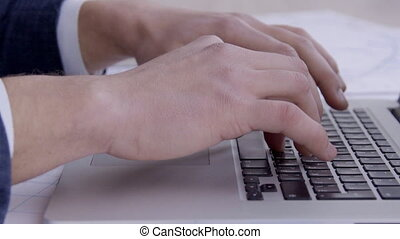Close-up of male hands typing text on laptop keyboard.