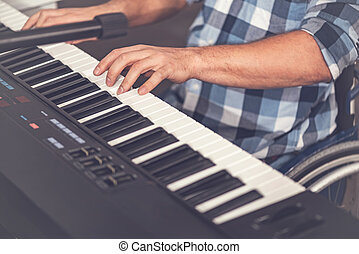 Close up of male hands while playing on electric piano