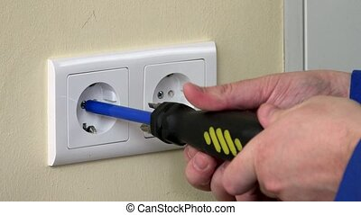 close up of male hands with screwdriver unscrew electrical outlet