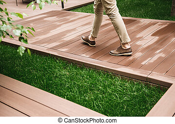 Close up of male legs walking on a wooden pathway