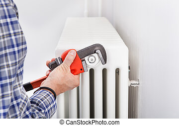 Plumber Fixing Radiator - Close-up Of Male Plumber Fixing...