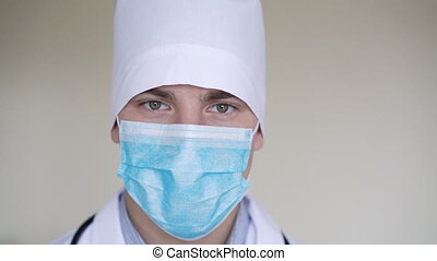 Close up of male surgeon's face dressed in surgical mask looking at camera in 4K