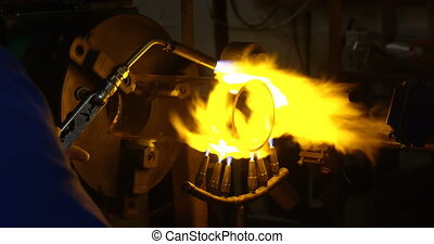 Close-up of male worker making glass in glass factory. Male worker heating glass 4k