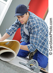 close up of male worker unrolling carpet in office