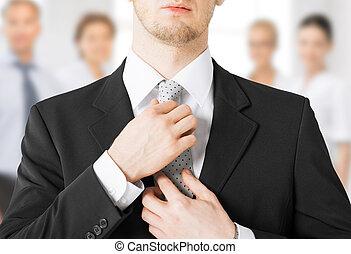 man adjusting his tie - close up of man adjusting his tie