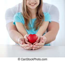 close up of man and girl holding red heart shape - people,...