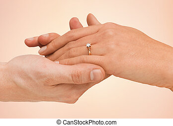 close up of man and woman hands with wedding ring