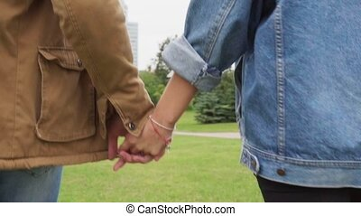 Close-up of man and woman holding hands and walking in a city park
