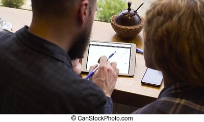 Close-up of man and woman studying a chart on a tablet while sitting in a cafe