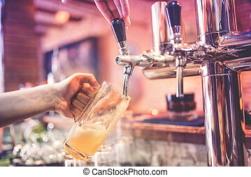 close-up of man, barman hand at beer tap pouring a draught ...