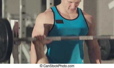 Close up of man building his muscles with a personal trainer at the gym