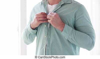 close up of man buttoning his shirt at home