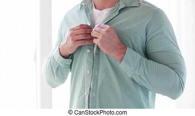 close up of man buttoning his shirt at home