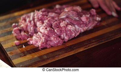 man cut pieces of raw meat - close up of man cut pieces of...