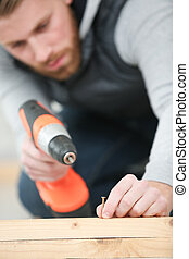 close up of man drilling nail on table