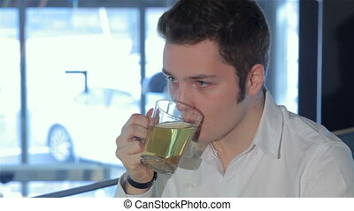 Close up of man drinks tea at the cafe