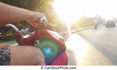 Close up of man driving motorbike on tropical island during...