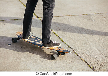 Close up of man foot riding longboard in park