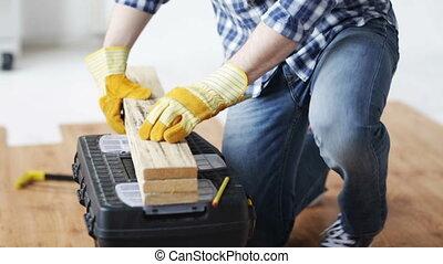 close up of man hammering nail to wooden board