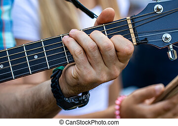 Close up of man hand playing guitar. Practicing in playing guitar