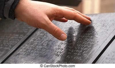 Close up of man hand reading with blind braille text. Disable people
