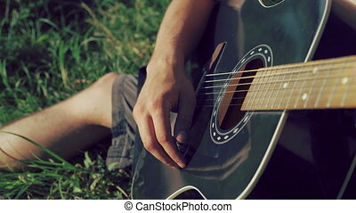 Close up of man hands playing the guitar on the nature. 4K