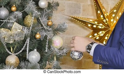 Close-up of man hanging decorative toy ball on Christmas tree branch