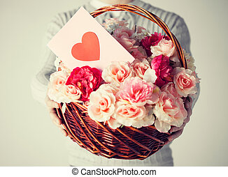 man holding basket full of flowers and postcard - close up ...