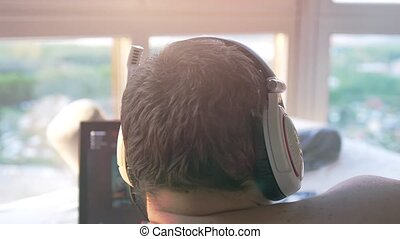 Close up of man in headphones working at home by notebook. slow motion