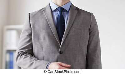 close up of man in suit adjusting necktie