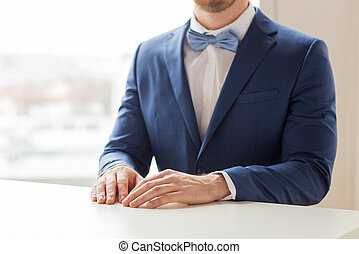close up of man in suit and bow-tie at table