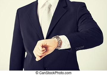 man looking at wristwatch - close up of man looking at ...