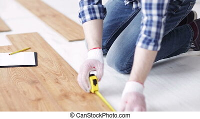 close up of man measuring flooring and writing