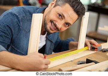 close up of man measuring wood flooring