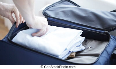 close up of man packing clothes into travel bag