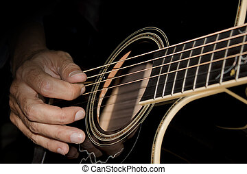 acoustic guitar - close-up of man playing a black acoustic ...
