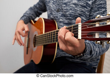 Close up of man playing acoustic guitar.