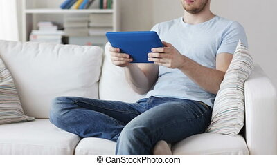 close up of man playing game on tablet pc at home
