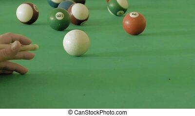 Close up of man playing pool billiard, snooker. Player hitting ball and it goes through the hole. Sports game of billiards in club as hobby and resting time.