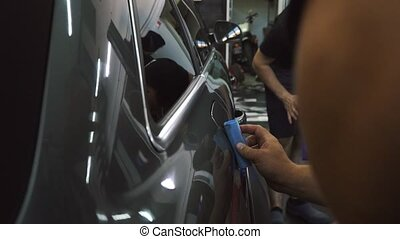 Close up of worker in dark uniform cleaning grey car with sponge at service station. Man polishing surface of modern automobile. Working process.