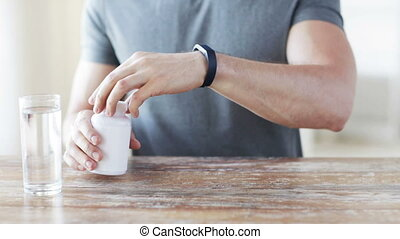 close up of man pouring pills from jar to hand