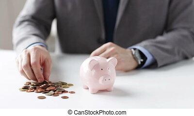 close up of man putting coins into piggy bank