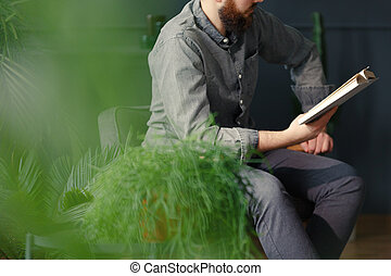 Close-up of man relaxing while reading book next to plants