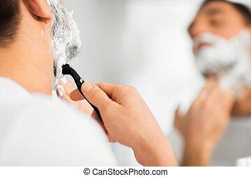 close up of man shaving beard with razor blade - beauty, ...