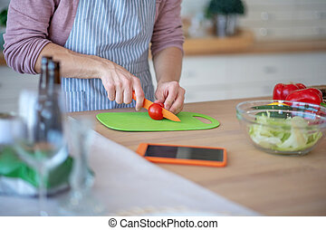 Close up of man slicing tomatoes while cooking salad