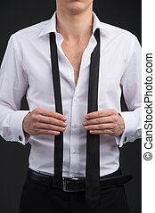 Close up of man starting tying a tie. Wearing classical...