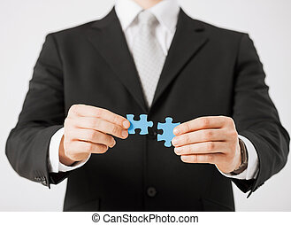 man trying to connect puzzle pieces